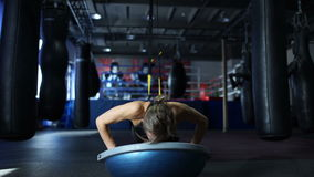 Woman in black sportswear doing push UPS on the Bosu and the TRX in gym stock footage