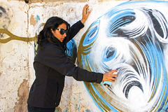 Woman in black spraying at a graffiti brick wall Stock Photography
