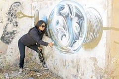 Woman in black spraying at a graffiti brick wall Royalty Free Stock Image