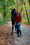 Woman black stallion horse avenue lane forest stock photo