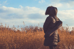 Woman in black standing alone in a field Royalty Free Stock Images