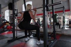 Woman in black stylish sportswear in sneakers crouches with a metal vulture on shoulders indoors. Girl doing strength exercises royalty free stock image