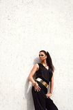 Woman in black suit with golden waistband posing on white backgr Royalty Free Stock Photography
