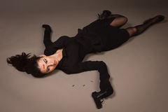 Woman in a black suit with gun lying on the floor Stock Photo