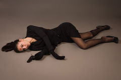 Woman in a black suit with gun lying on the floor Royalty Free Stock Photos