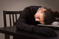 Woman in a black suit lying on a table Stock Images