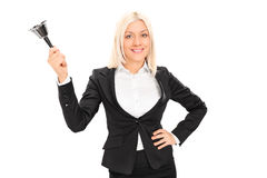 Woman in black suit ringing a lunch bell Royalty Free Stock Image