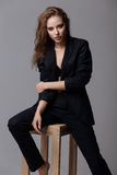 Woman in black suit sits on a chair Royalty Free Stock Image