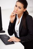 Woman in black suit sitting in front of computer Stock Photo