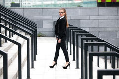 Woman in black suit walking on stairs with railings at street Royalty Free Stock Photo