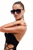 Woman in black sunglasses and swimsuit wearing golden bracelet with hair up poses on isolated white background. Fashion. Tan model. Beautiful awesome cool girl Royalty Free Stock Photography