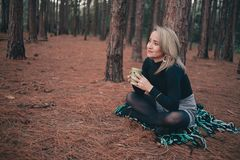 Woman in Black Sweater Sitting on Brown Ground While Holding Cup stock image