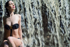 Woman in black swimsuit enjoying a waterfall Royalty Free Stock Photography