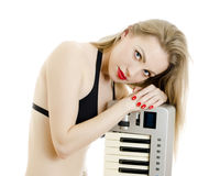 Woman in black swimsuit posing with Piano Royalty Free Stock Images
