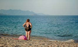 Woman in Black Swimsuit Standing on Beach Shore Stock Photography