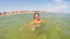 A woman in a black swimsuit swims in the sea near the shore stock video