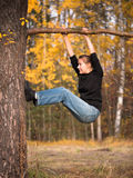 A woman in a black T-shirt hanging on a branch and doing exercises Stock Photo