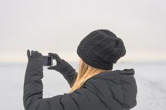 Woman in black. Woman taking pictures on the phone winter landscape Royalty Free Stock Photos