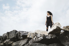 Woman in Black Tank Top and Black Pants Standing on the Rock Mountain during Daytime Stock Image