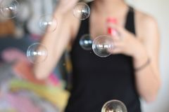 Woman in Black Tank Top Blowing Soap Bubble Royalty Free Stock Photos