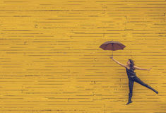 Woman in Black Tank Top Holding an Umbrella in Front of Yellow Concrete Wall Stock Photo