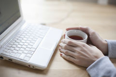 Woman With Black Tea And Laptop On Table Stock Images