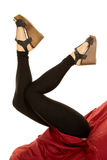 Woman in black tights and heels legs up red sheet Stock Photo