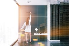 Woman in a black tile bathroom interior. Rear view of a woman standing in a bathroom interior with black tiles and a loft window. 3d rendering toned image double royalty free stock photography