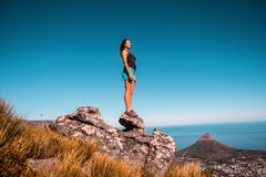Woman in Black Top and Blue Shorts on Stone Under Blue Sky stock photography