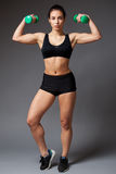 Woman in a black top holding dumbbells stock images
