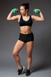 Woman in a black top holding dumbbells royalty free stock image