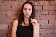 The woman in black top poses near a brick wall Royalty Free Stock Photos