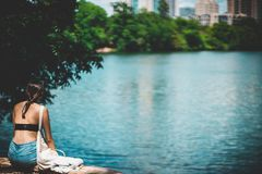 Woman in Black Top Sitting Beside Body of Water Stock Photo