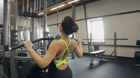 Woman in black training suit pumps iron in Fitness-station in gym. stock footage