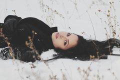 Woman in Black Trenchcoat Laying on White Snow Stock Images
