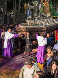 Easter Procession Antigua. A woman in black and two men in purple robes lead a procession of women carrying a heavy wooden structure as part of Semana Santa ( Royalty Free Stock Photography