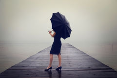 Woman with black umbrella looking infinity in a surreal place. Woman with black umbrella looking infinity royalty free stock photos