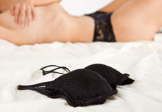 Woman in black underwear lay on bed Stock Photography