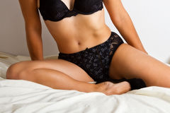 Woman in black underwear lay on bed Stock Photo