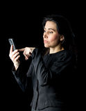 Woman in Black Using Cell Phone. Brunette woman in black dress and black gloves standing in front of a black backdrop and looking at a cell phone Stock Photo