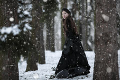 Woman in black Victorian dress. In the winter park stock image