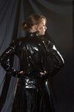 Woman in black vinyl costume stock image