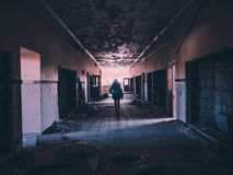 Woman in Black Walking in Hallway Stock Image