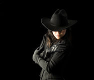 Woman in Black Wearing Cowboy Hat. Brunette woman in black dress and black gloves, wearing a black cowboy hat, holding her arms across her body and looking Royalty Free Stock Image