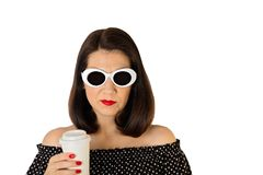 Woman in a black and white dress with polka dots and white sunglasses holding a glass of coffee. royalty free stock photography