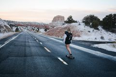 Woman in Black and White Long Sleeve Shirt Riding a Skateboard on a Freeway Road Royalty Free Stock Photo
