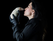 Woman in Black with White Rat. Brunette woman in black standing in front of a black backdrop, holding a white dumbo rat, looking at it with affection and love Stock Photos