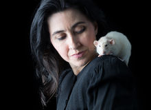 Woman in Black with White Rat. Woman in black standing in front of a black backdrop with a white dumbo rat perched on her shoulder Stock Photos