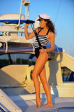 Woman in black and white swimsuit  standing on the deck and holding binoculars. Royalty Free Stock Photo