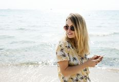 Woman in Black Yellow and White Floral Button-up Shirt Holding Smartphone Wearing Aviator Sunglasses Near Body of Water Stock Photography